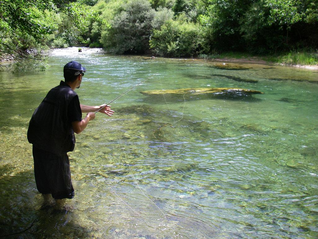pêcheur à la mouche dans une petite rivière des cévennes aux eaux limpides