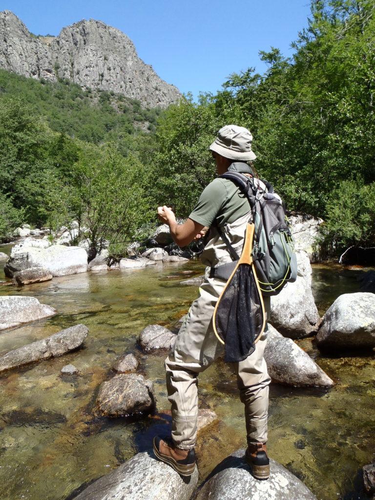 un pêcheur à la mouche dans les gorges de la Dourbie traque les truites farios sauvages dans un endroit naturel préservé